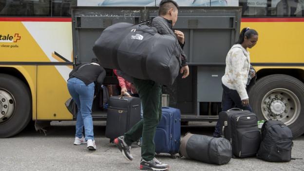 Flüchtlinge nehmen ihr Gepäck aus einem Postauto.