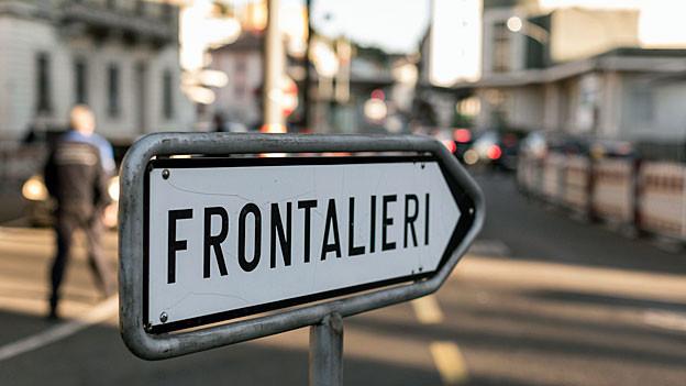 Auf einem weissen Wegweiser in Chiasso steht in schwarzer Schrift: «Frontalieri», deutsch: Grenzgänger.