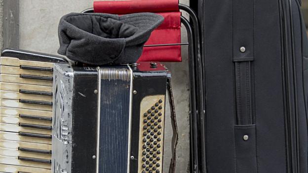 Auf dem Bild sieht man eine Mütze mit Kleingeld auf einem Akkordeon, ein Kalppsitz und ein Koffer.