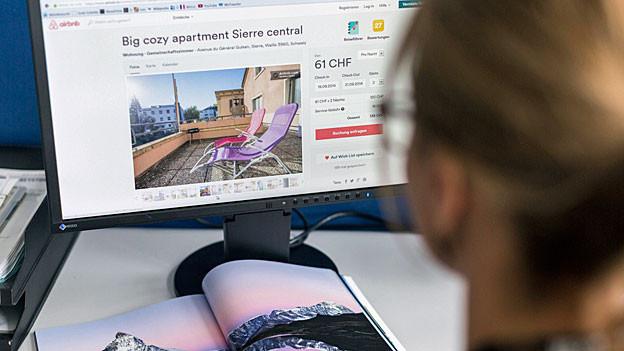 Eine junge Frau sitzt vor einem Computer; auf dem Bildschirm sieht man die Homepage von Airbnb.