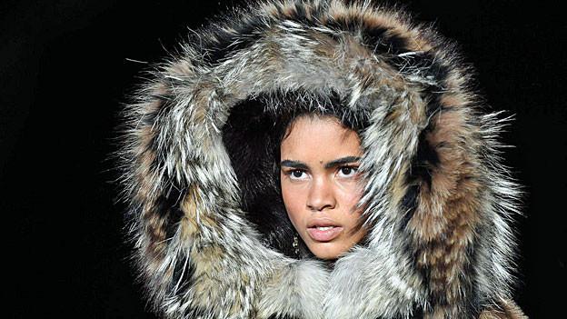 Ein Model präsentiert eine Jacke, deren Kapuze mit einem mächtigen Pelz geschmückt ist.