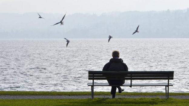 Ein Mann sitzt alleine auf einer Bank am Seeufer