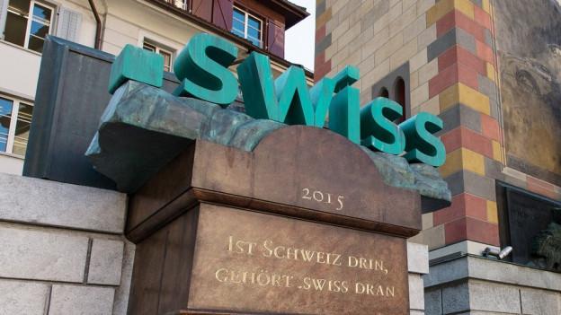 Das .swiss-Logo, platziert auf einem Sockel.