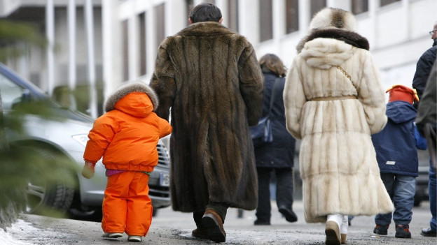 Eine Familie in Pelzmänteln in den Strassen von St.Moritz.