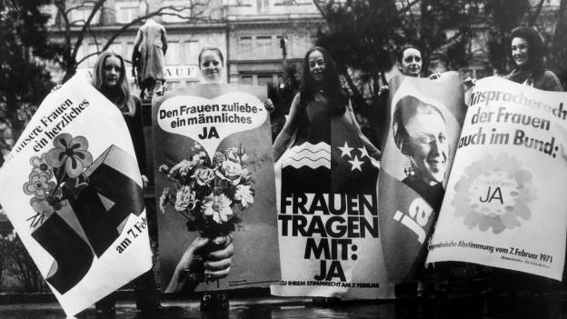 Frauen werben mit Plakaten für das Frauenstimmrecht.