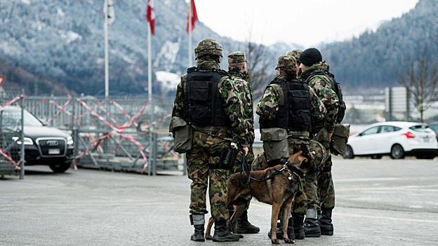 Sicherheitskräfte der Schweizer Armee stehen mit einem Hund auf einem verschneiten Platz.