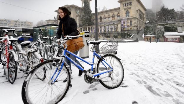 Eine Frau läuft mit ihrem Fahrrad über einen schneebedeckten Platz.