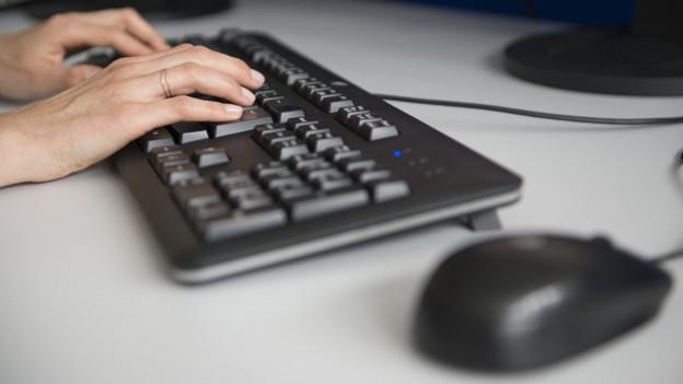 Das Bild zeigt zwei Hände auf einer Computertastatur, im Vordergrund eine Computermaus.