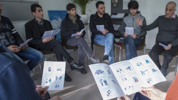 Bewohner eines Asylzentrums werden über den neuen Flyer informiert.