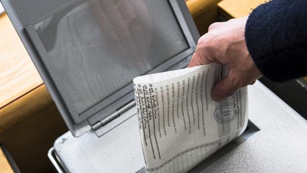 Ein Wähler wirft seinen Wahlzettel in eine Urne.