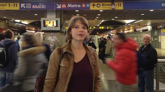 Junge Frau vor vorbeieilenden Menschen im Römer Hauptbahnhof.