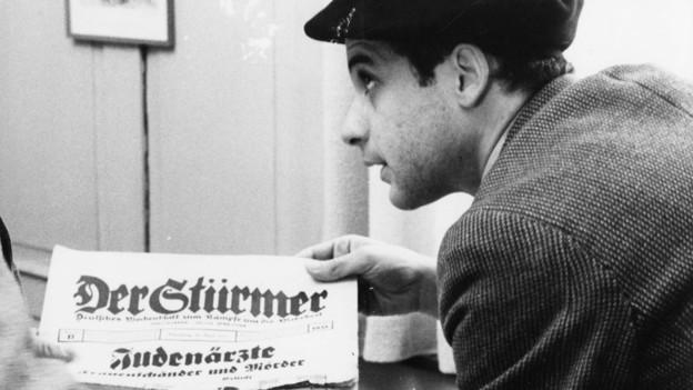 Junger Mann mit Zeitung «Der Stürmer» mit einer Titelgeschichte über jüdische Ärzte.