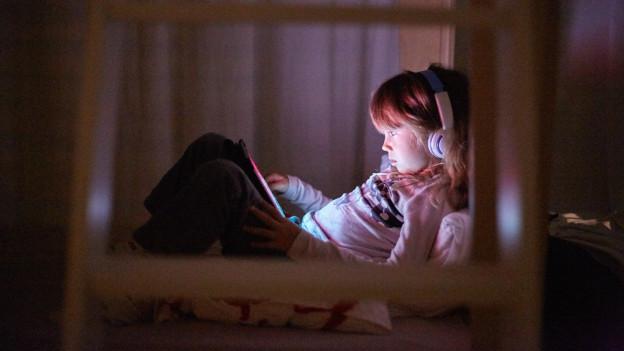 Ein Mädchen sitzt im Bett und schaut sich Videos an