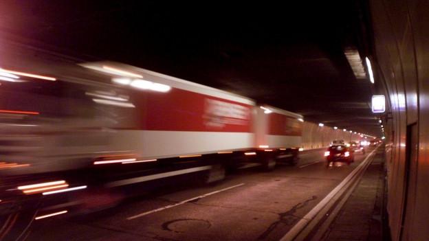 Lastwagen fahren mit hoher Geschwindigkeit durch einen Tunnel.