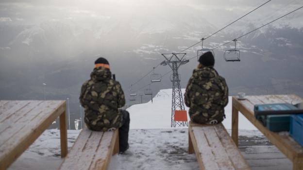 Zwei Personen schauen an einer Bahn vorbei den Hang hinab.