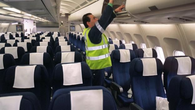 Mann begutachtet Gepäckaufbewahrung in Flugzeugkabine.