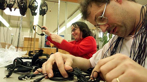 Arbeit für IV-Bezüger und IV-Bezügerinnen: Ein Mann und eine Frau rezyklieren alte Kopfhörer.
