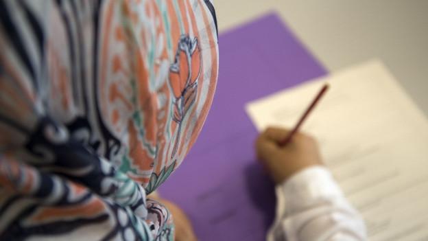Eine Schülerin mit Kopftuch.