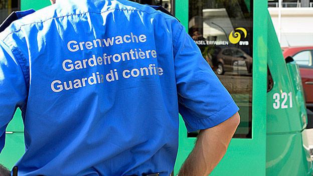 Ein Schweizer Grenzwächter steht vor einem Basler Combino-Tram. Auf dem Rücken seines blauen Hemds steht «Grenzwache, Gardefrontière, Guardia di Confine».