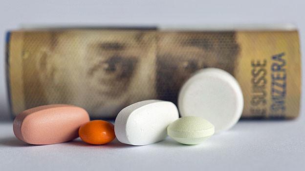 Verschiedene Tabletten liegen vor einer gerollten 200-Frankennote auf einem Tisch.