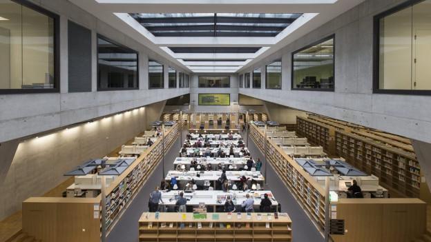 Archivaufnahme der Bibliothek der pädagogischen Hochschule Bern, eine Weitwinkelaufnahme eines grossen Raumes, unten sind Studentinnen und Studenten am Arbeiten.