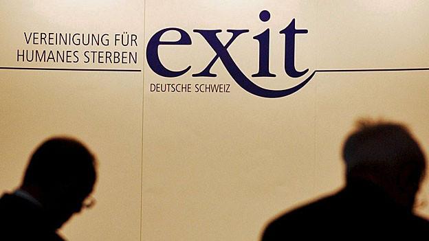 Vor dem Exit-Logo sind die Schatten zweier Köpfe zu sehen.
