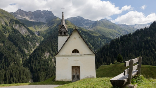 Eine Kappelle im bündnerischen Val Lumezia vor Bergkulisse.