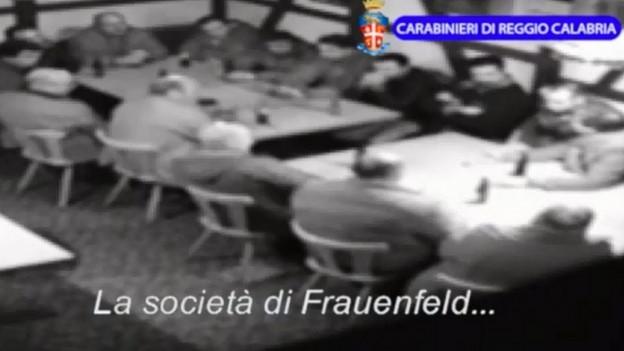 Ein Dutzend Männer sitzen im August 2014 um zwei Tische, vermutlich in einem Restaurant.