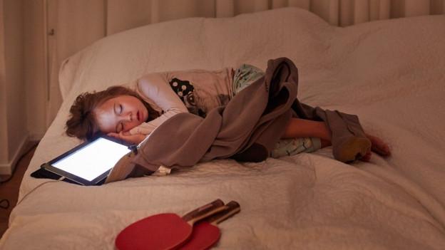 Ein Kind schläft auf dem Bett neben einem eingeschalteten Laptop.