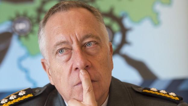 Der Armeechef hält sich den Finger an die Lippen und denkt nach.