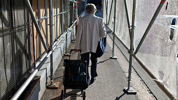 Eine ältere Frau mit einem Einkaufswagen geht unter einem Baugerüst vorbei.