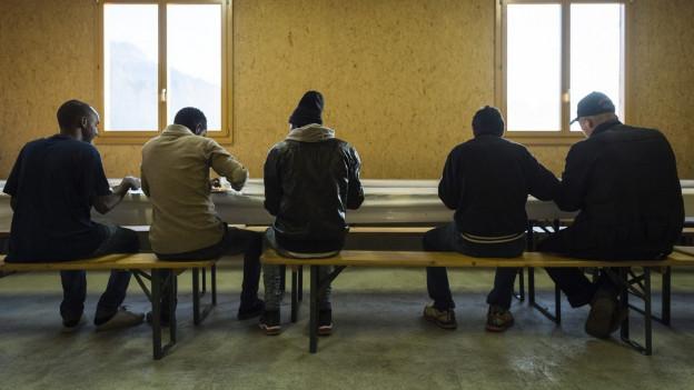 Das Bild zeigt Flüchtlinge in einem Asylzentrum beim Frühstück.