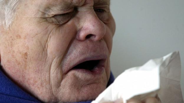 Ein älterer Mann niest in ein Taschentuch.