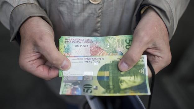 Zwei Banknoten in den Händen eines älteren Mannes.