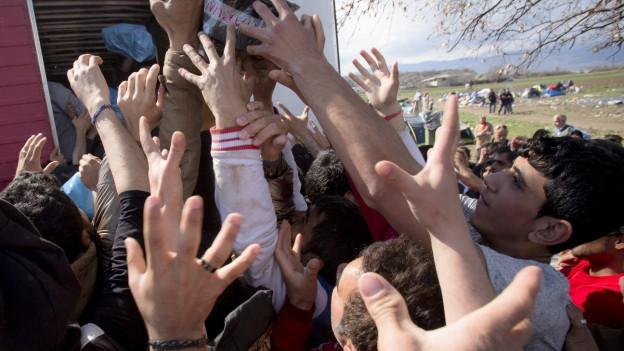 Migranten strecken ihre Hände aus, um an Hilfslieferungen zu kommen.