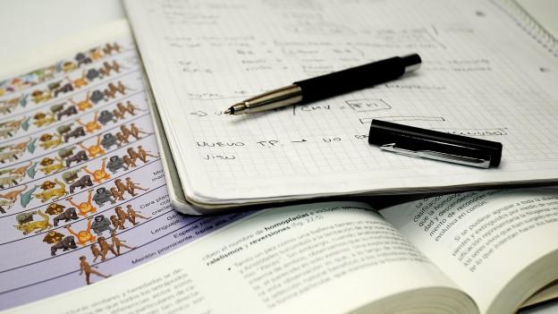 Aufgeschlagenes Biologie-Buch, darauf liegt ein Heft und ein Stift.