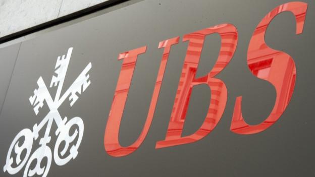 Zu sehen ist das rote Logo der Grossbank UBS auf einer grauen Hausfassade.