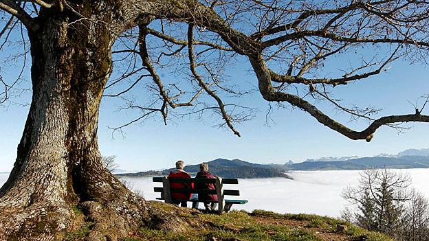 Ein älteres Paar sitzt auf einer Bank über einem Nebelmeer und blickt auf die Alpen.