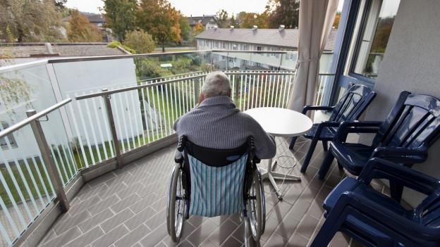 Ein alter Mann sitzt im Rollstuhl auf einer Terrasse.
