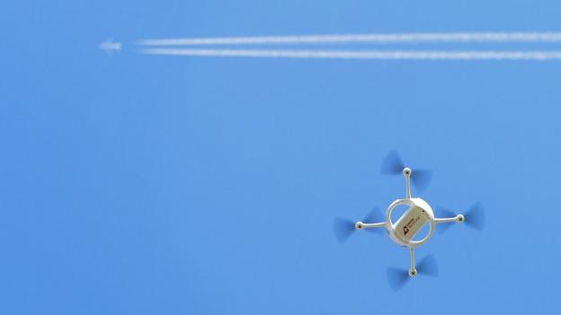 Eine Drohne der Post am blauen Himmel, darüber fliegt ein Flugzeug vorbei, man sieht den weissen Kondensationsstreifen (7. April 2015).