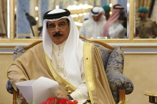 Der König von Bahrain in traditioneller Kleidung und mit Kopftuch auf einem Sessel, ein Papier in der Hand (7. April 2015).