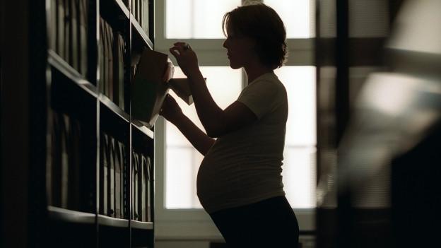 Eine Hochschwangere steht vor einer Wand mit Archivmaterial, sie steht im Gegenlicht, man sieht nur ihre Silhouette (Symbolbild 2003)