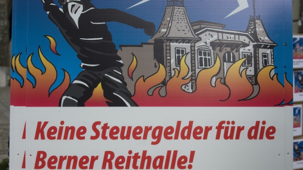 Plakat, das krawallierenden Chaoten zeigt. Flamen im Hintergrund.