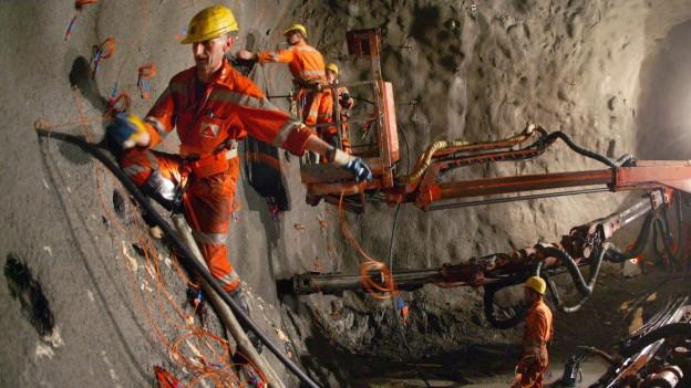 Arbeiter im Tunnel, die Sprengstoff in die Wand legen.