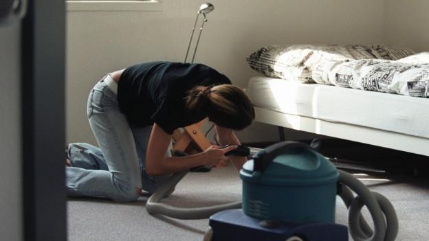 Eine junge Frau kniet auf dem Boden und saugt Staub unter einem Bett.