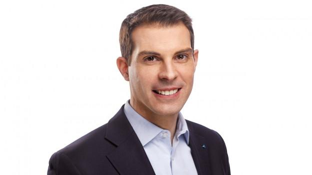Thierry Burkart lächelt in die Kamera, er trägt ein hellblaues Hemd und einen schwarzen Anzug.
