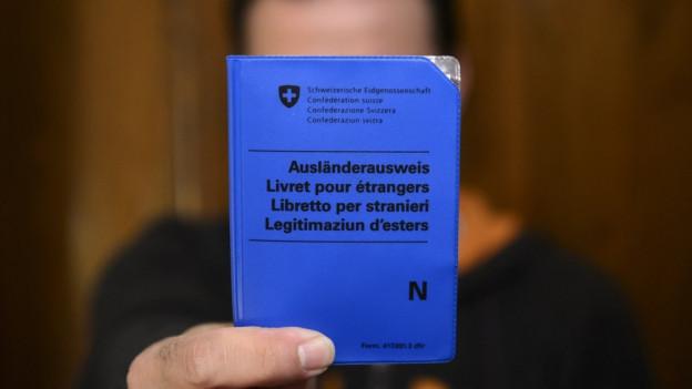 Ein Mann hält einen N-Ausländerausweis in die Kamera.