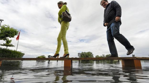 Menschen gehen über einen Notsteg wegem Hochwasser im Hafen in Gottlieben im Kanton Thurgau. Der Bodensee steigt weiter an.