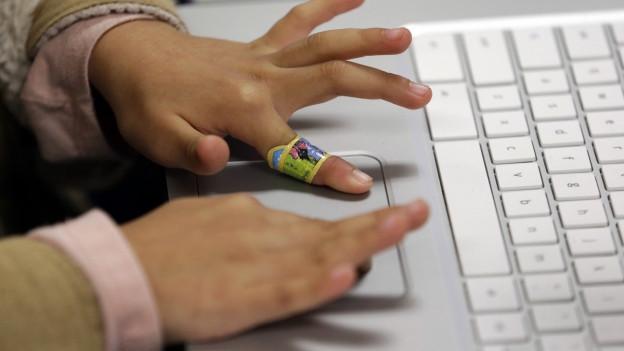 Kinderhände auf einer Computertastatur