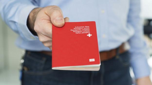 Ein Mann hält einen Schweizer Pass in der Hand